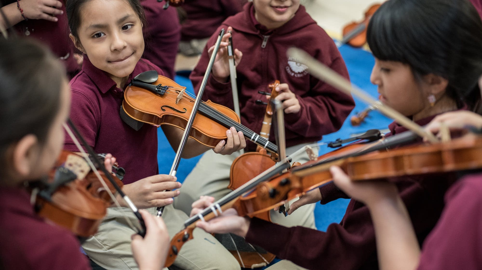 Ivanna Benitez, 7, practices her violin with her friends before class.