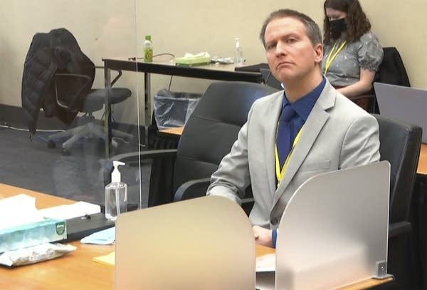 A man listens in a courtroom.
