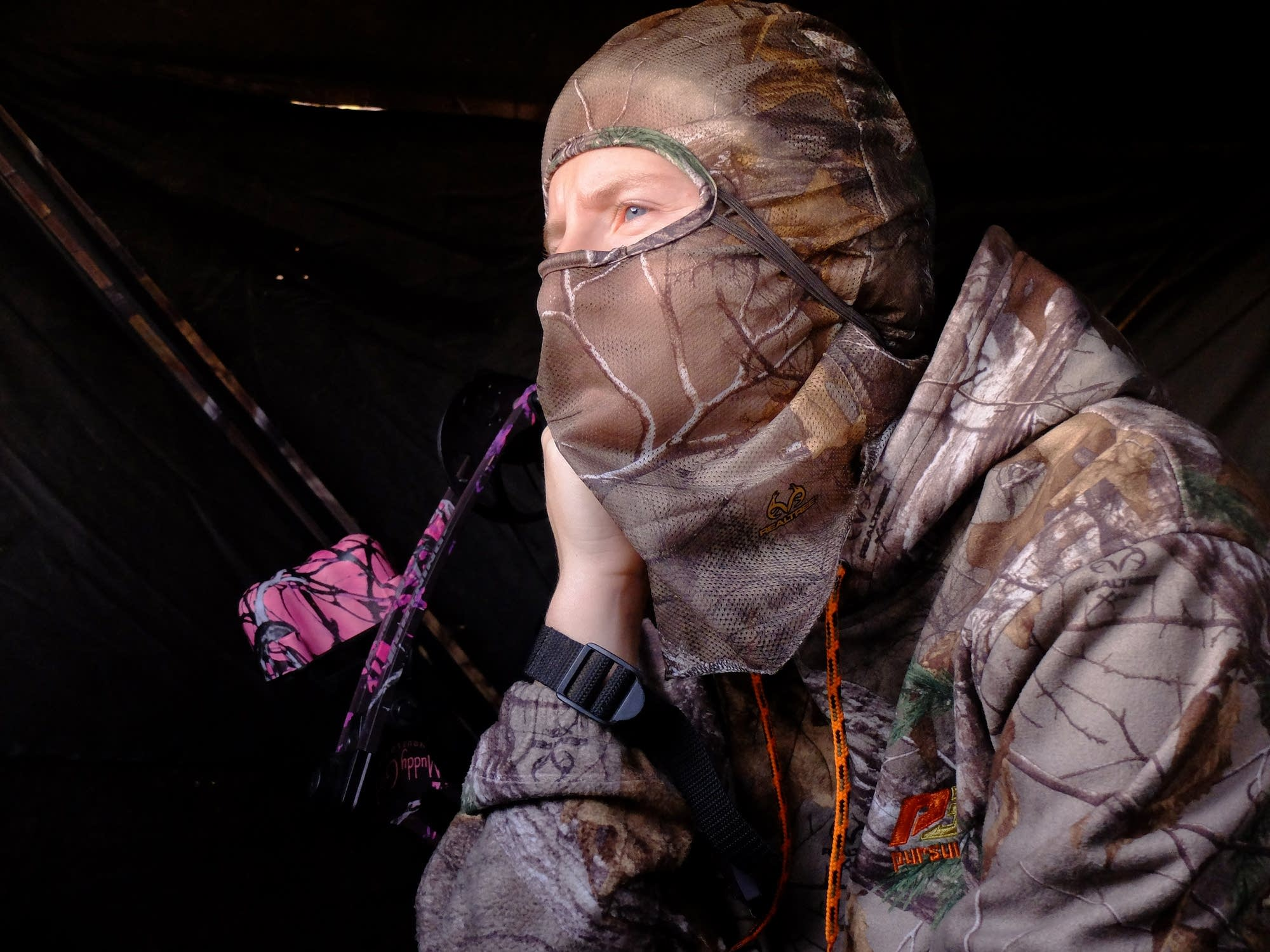 Misty Stoll scans the area as she waits for a deer to pass her blind.