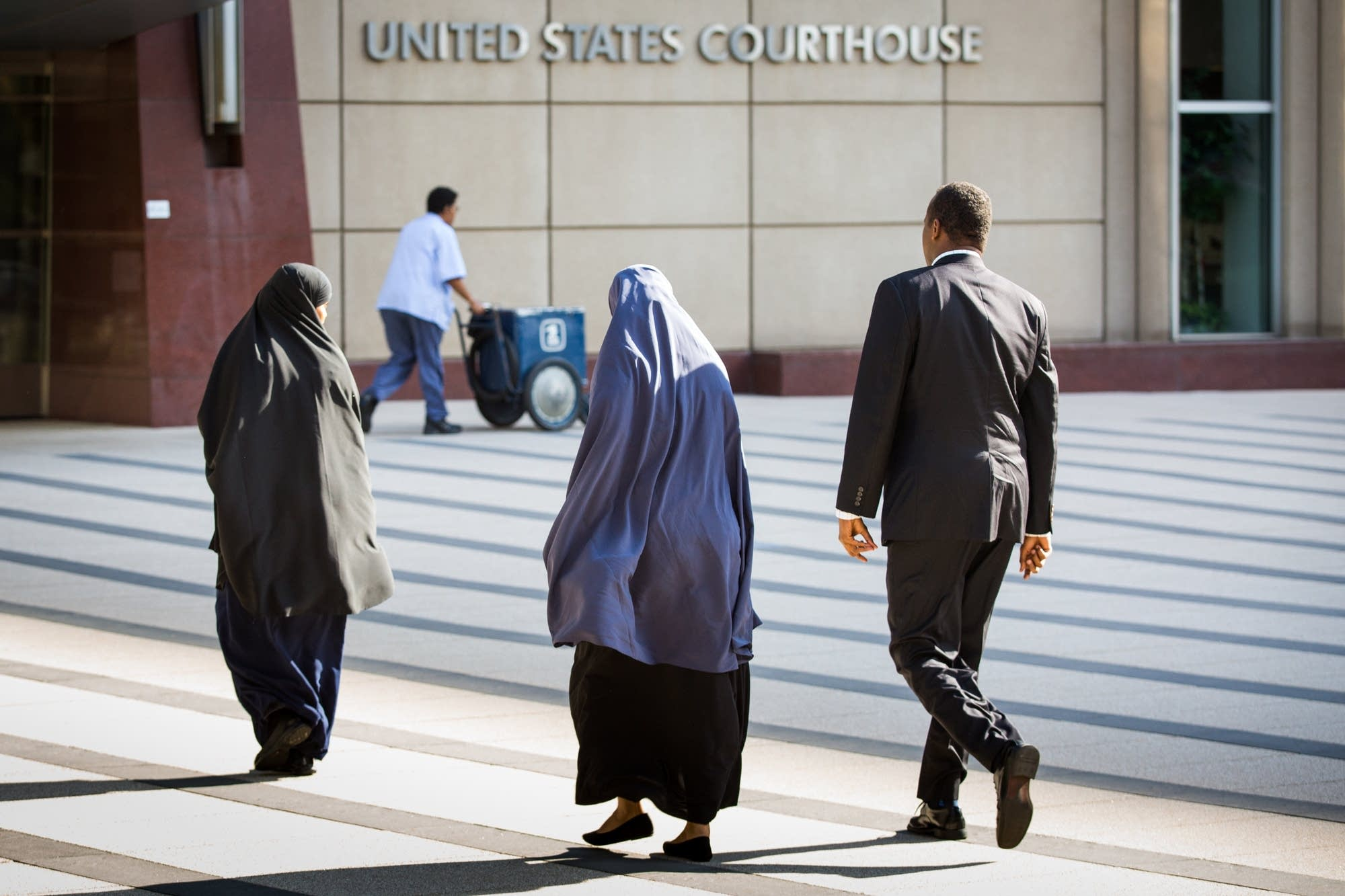 Three people enter the Federal Courthouse.
