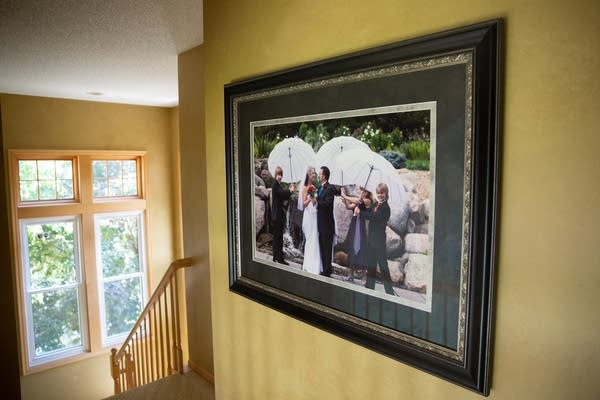 A wedding photo hangs on a yellow wall.