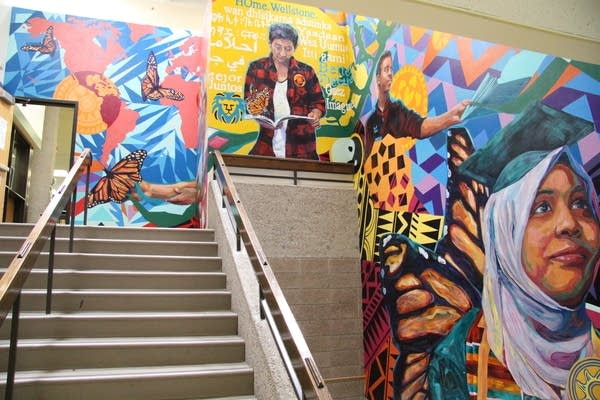 A mural is painted in the staircase of a school