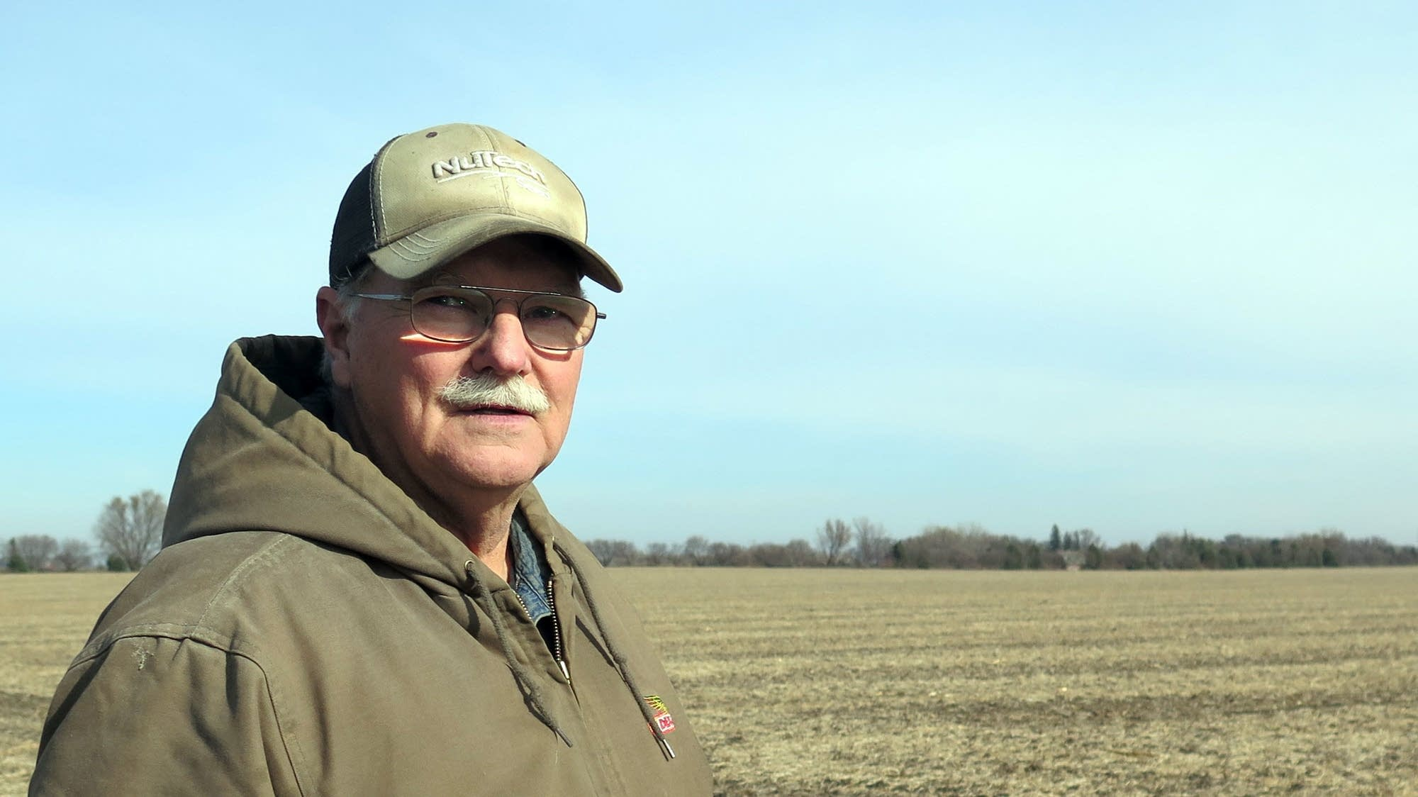 Tom Peterson stands on his farm, near Trimont