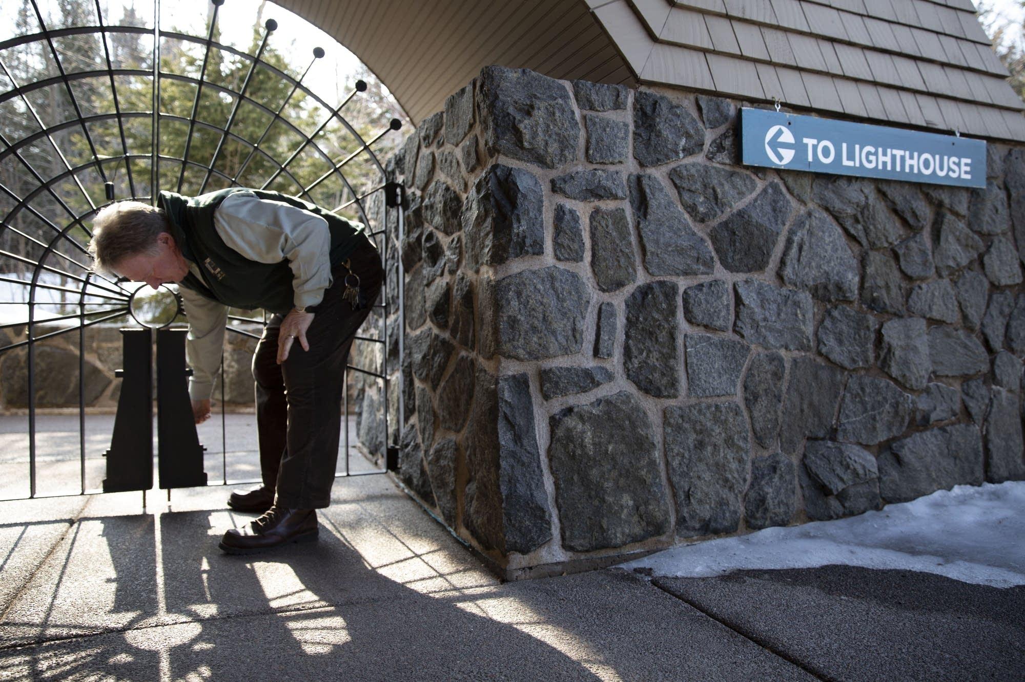 Lee Radzak opens a gate to the Split Rock Lighthouse.