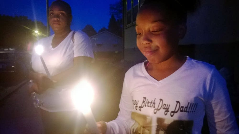 Angel Gaddy lights a candle to honor her father.