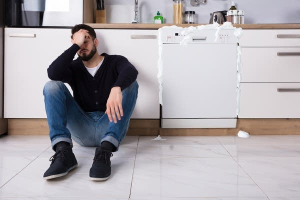 White man w/ beard sits sadly next to his broken dishwasher