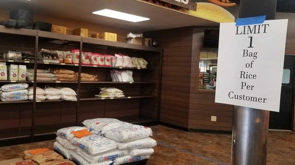 """A sign reads """"Limit 1 bag of rice per customer"""" near bags of rice."""