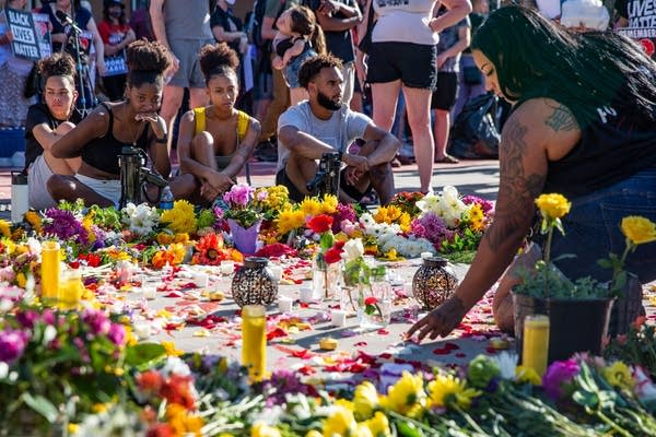 People sit near a circle of flowers on the ground.