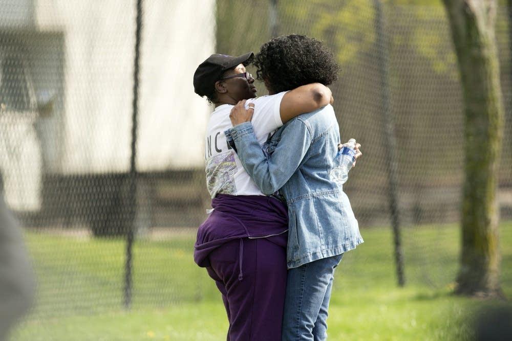 Two women hug outside of the memorial.