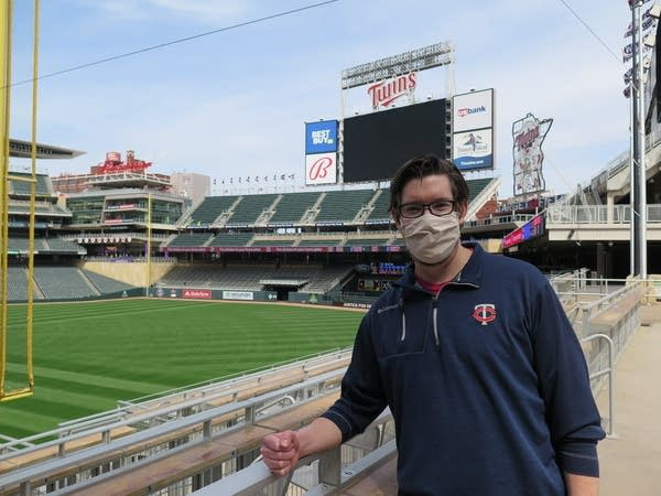 A man wearing a mask poses for a photo at Target Field.