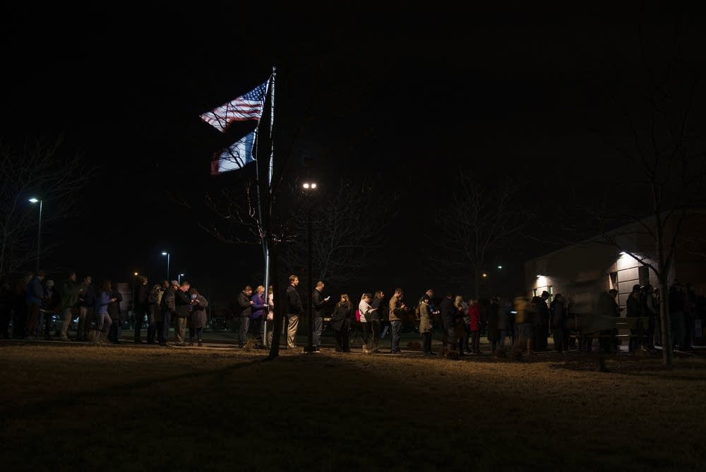 Caucus-goers line up outside an elementary school.