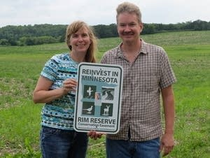 Rob and Loreli Westby stand with a sign.