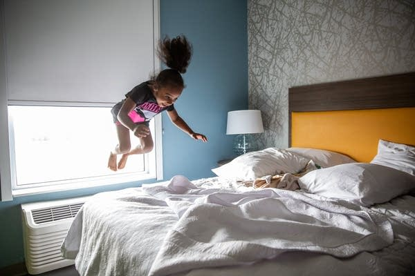 A young girl jumps on a bed.