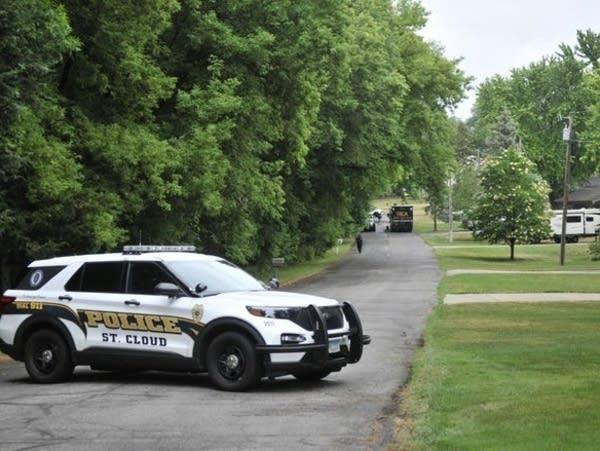 A police vehicle blocks a drive in a neighborhood