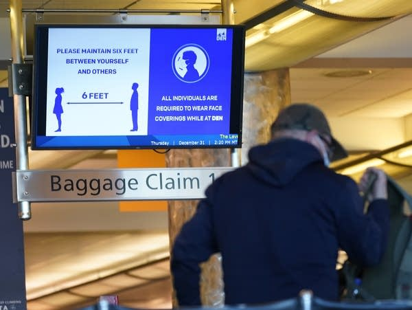 An electronic sign advises travelers to wear face masks