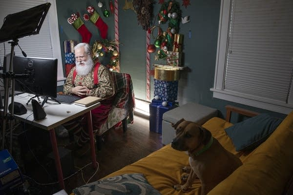 A man dressed as Santa sits in front of monitors at a home office.