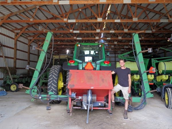 Scott Haase stands with a cover crop planter at his family's farm.