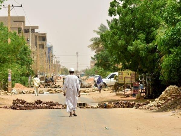 Sudanese residents walk past barricades in Khartoum