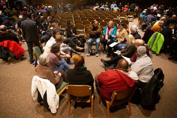 People sit in a circle inside of a church sanctuary.