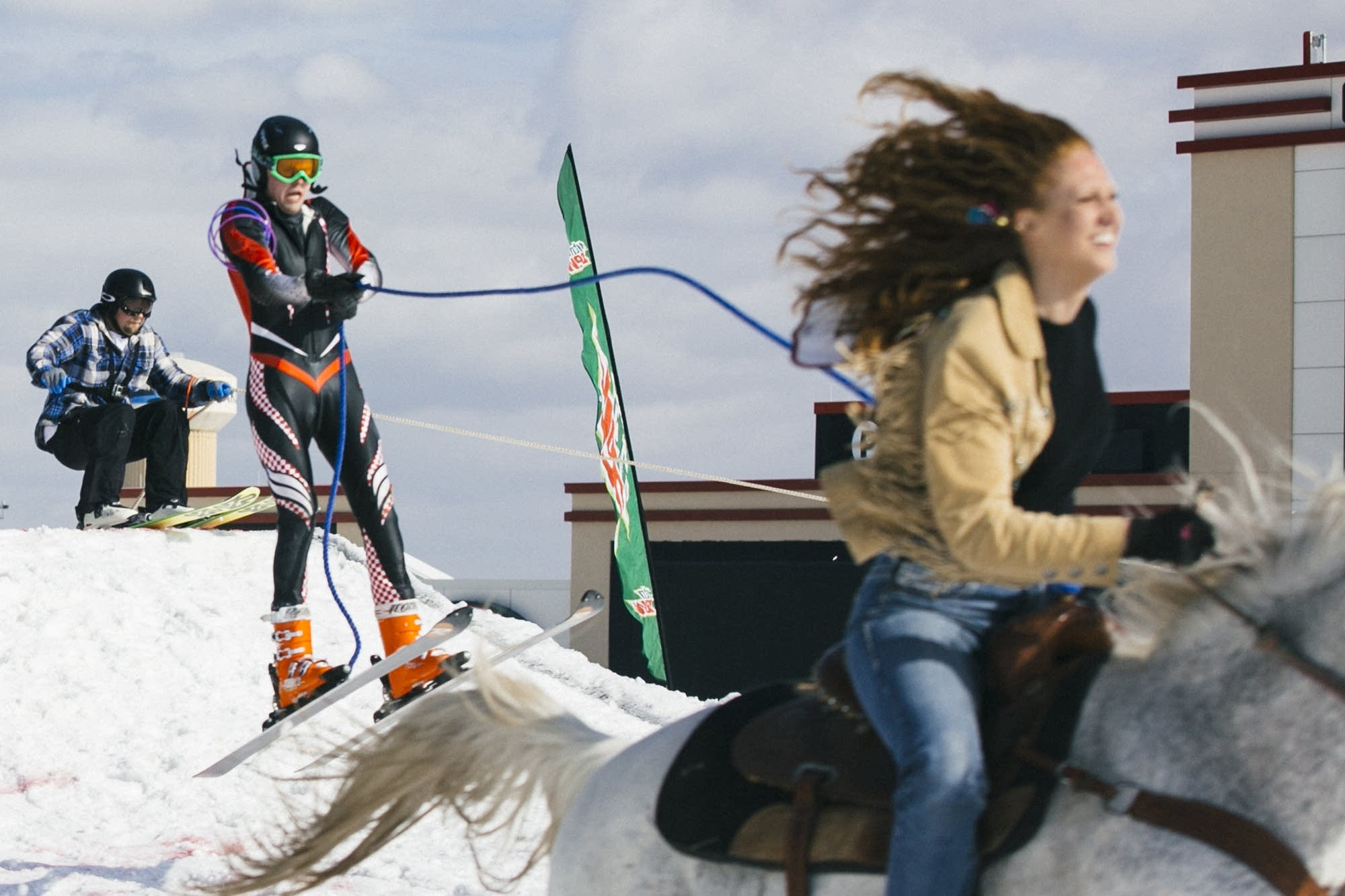 Riders pulls their skiers over a jump in the course.