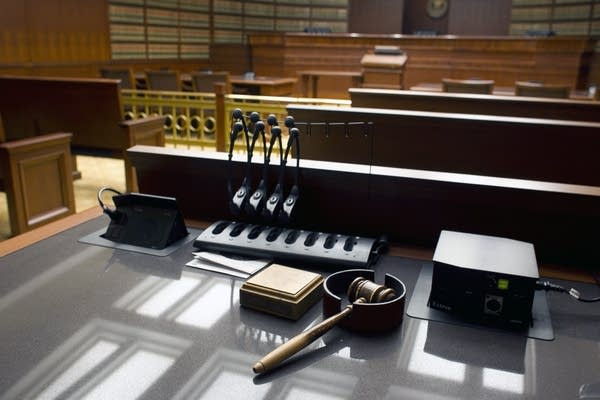 A gavel sits on a desk inside a courtroom.