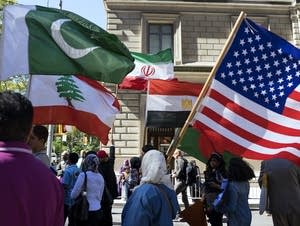Marchers carry the national flags during the Muslim Day Parade
