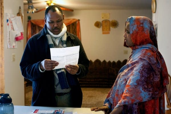 Social worker Abdulahi Mohamed helps Safiya Mohame