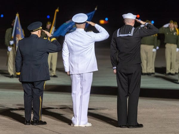 Honor guard members salute the arrival of Dante Tini late Thursday night