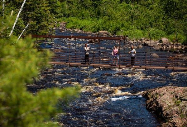 Visitors to Tettegouche State Park cross the suspension bridge.
