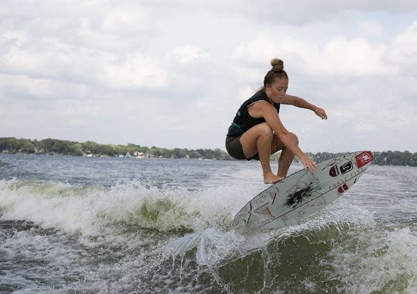 A woman jumps out of the water with a wakesurf board.