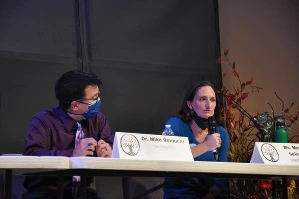 Two people sit at a table. One wears a mask, the other speaks into a mic.