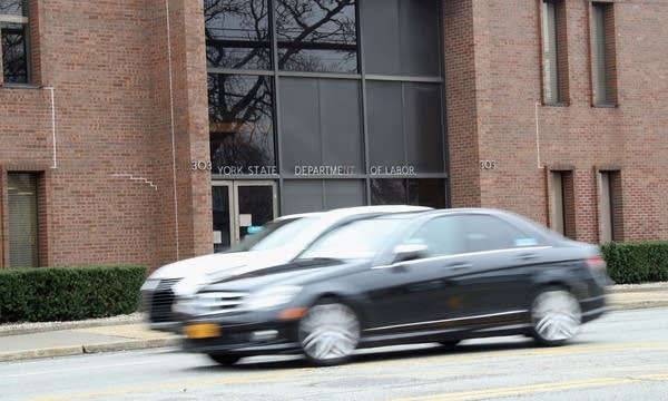 Cars speed past the New York State Department of Labor.