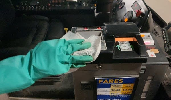 A person wearing gloves cleans a fare box.