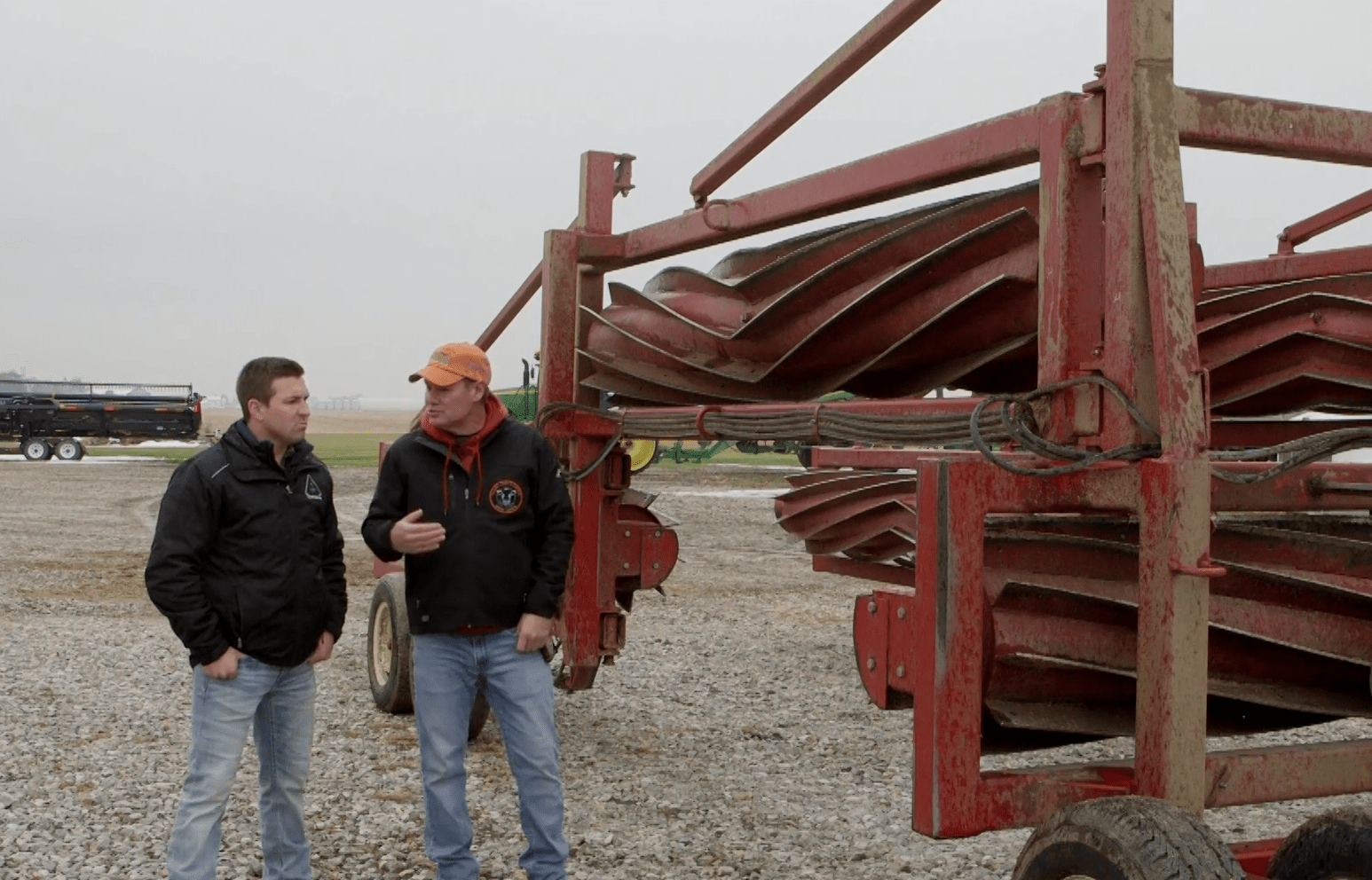 Rick Clark and Mitchell Hora stand in front of machinery on Clark's farm