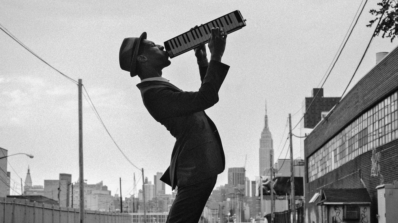 Jon Batiste carries his melodica