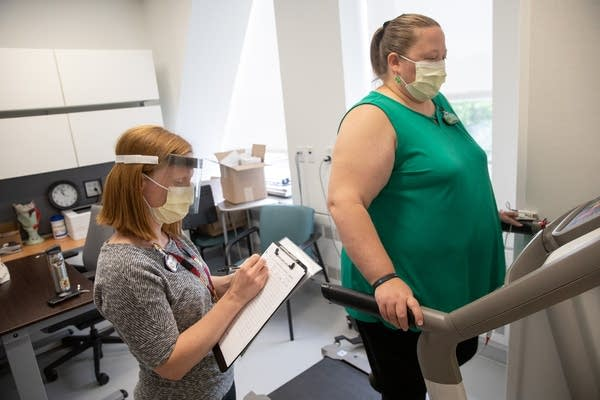 A woman walks on a treadmill as another holds a clipboard.