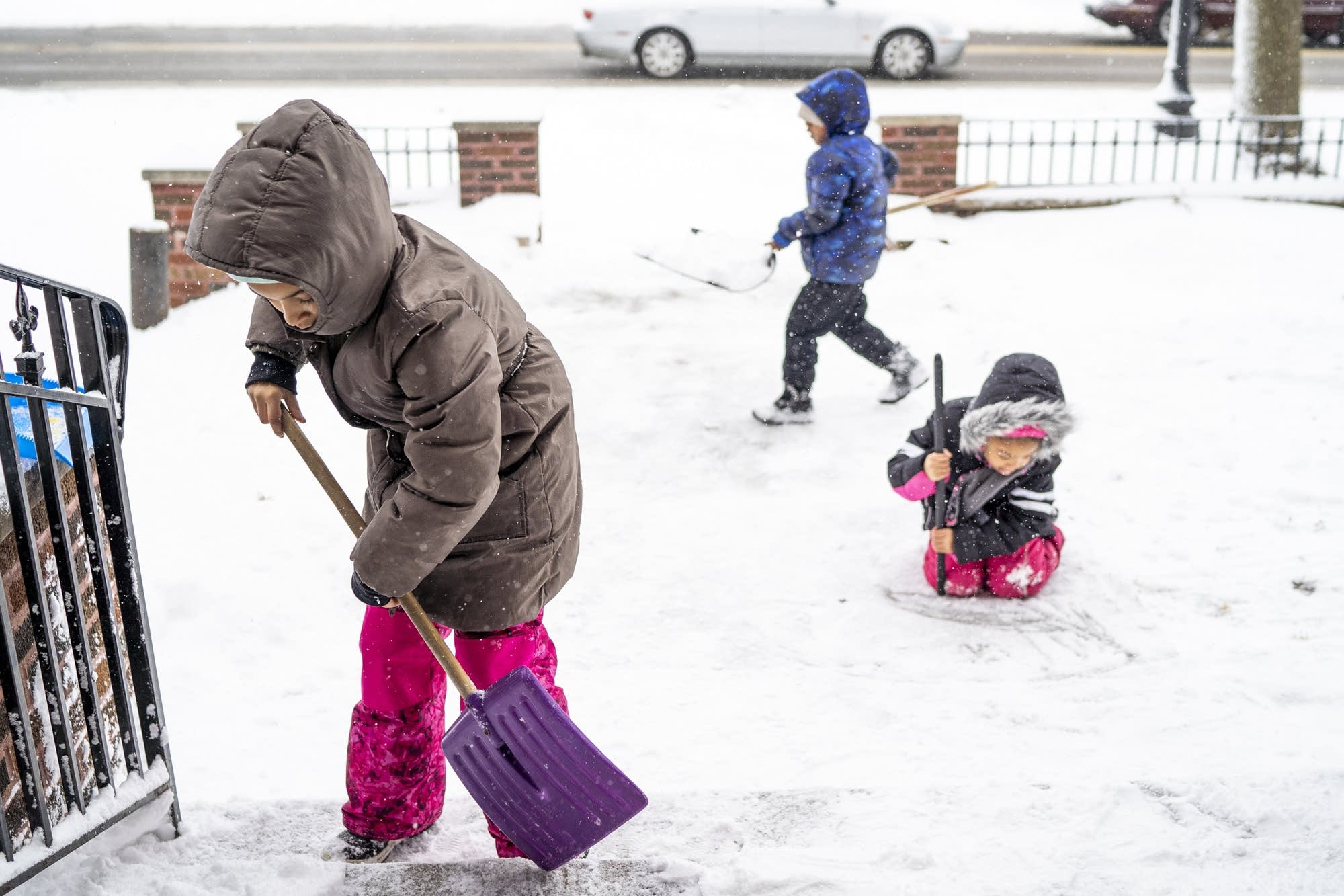 Azaria, 9, Khalil, 4, and Shawntaya, 6, help shovel snow.