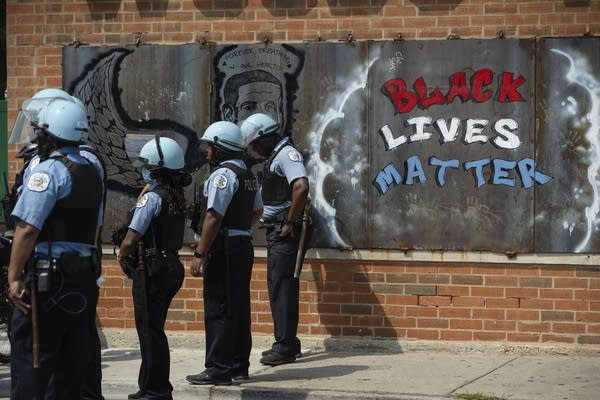 Police officers stand beside a mural for George Floyd.
