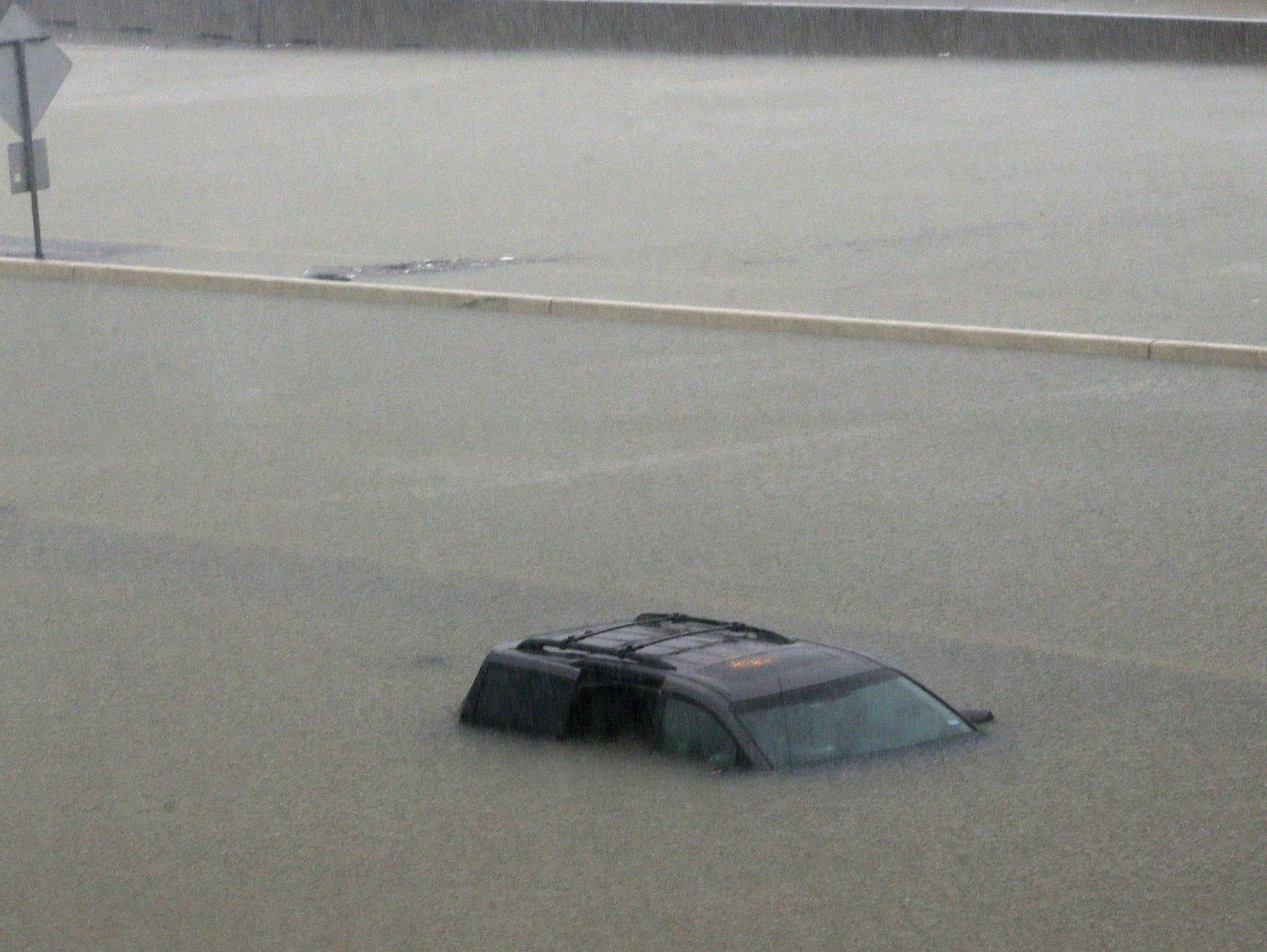 An abandoned vehicle sits in flood waters on the I-10 highway