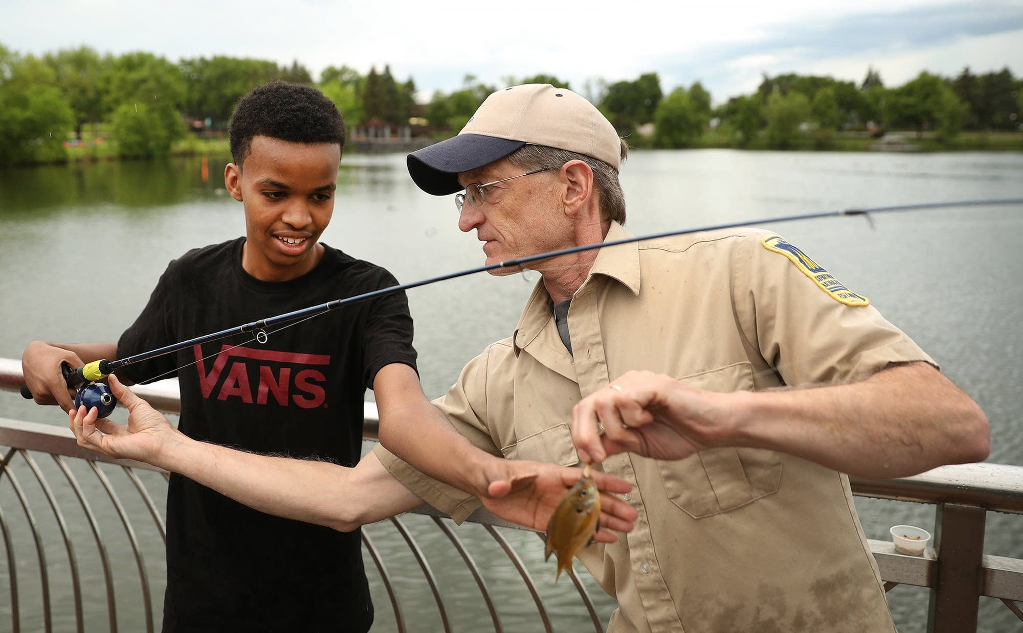 Mark Pelham helps Abdulahi Ahmed, 16 with removing his first catch.