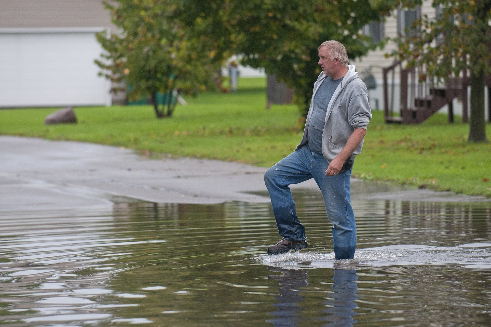 Mike Johnson walks through a flooded street.
