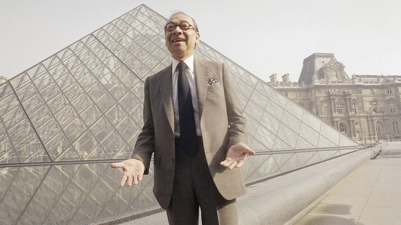 Architect I.M. Pei stands in front of the Louvre museum's glass pyramid.