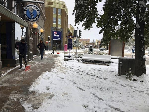 People clear the sidewalk after a fall snowstorm in Montana.