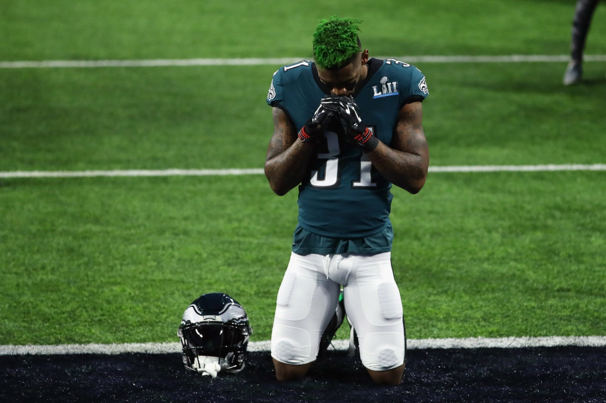 Jalen Mills (31) of the Philadelphia Eagles kneels on the field.