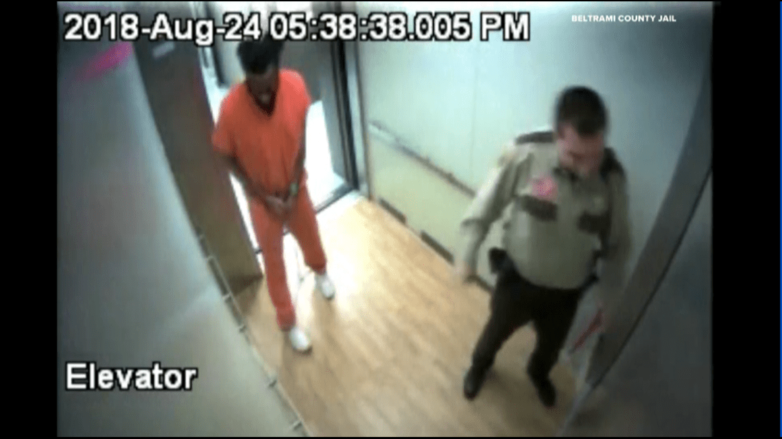 A video screenshot of a man in an orange jumpsuit and an officer.