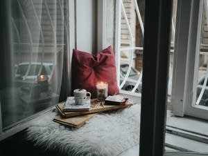 Cozy windowsill with candle and hot chocolate
