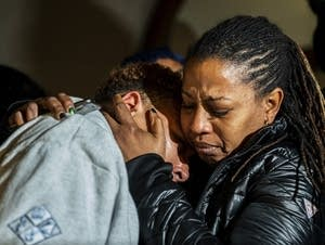 Christian Carter (left) is consoled by an unidentified woman
