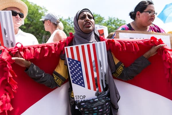 22-year-old Zaynab Abdi, a refugee from Yemen, holds up her country's flag.