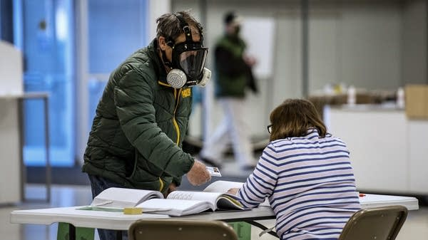 A man wears a full face mask as he presents his ID to a poll worker.