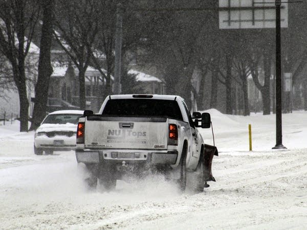 Cars and snowplows drive down a snow-covered street.